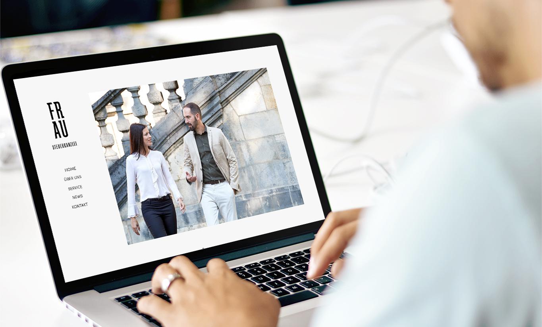 Blick auf einen Laptop. Man sieht eine Seite der Kanzlei Website. Miguel Frau und Kollegin laufen am Friedensengel in München.