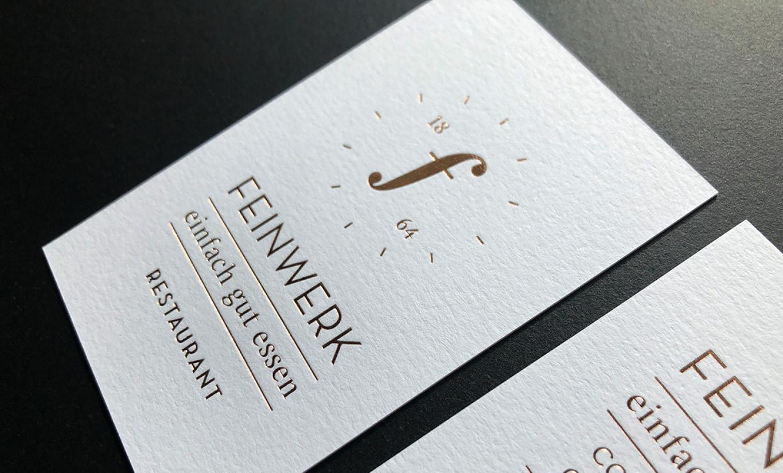 Weiterer Bestandteil des Corporate Design.Visitenkarten für das Restaurant Feinwerk. Weißes, offenes Papier von Gmund. Darauf das Logo und die Informationen in goldener Heißfolienprägung.
