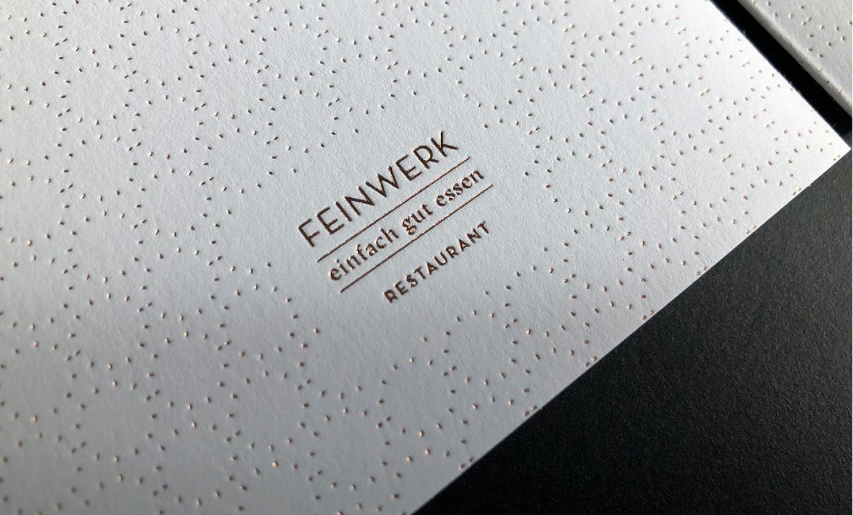 Ausschnitt des Gutscheins. Goldene Heißfolienprägung des Logos und des Designelements.