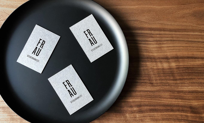 Graue Visitenkarten mit schwarzem Logo, geprägt mit Heißfolie. Die Karten liegen in einer schwarzen Schale auf einem Holztisch.