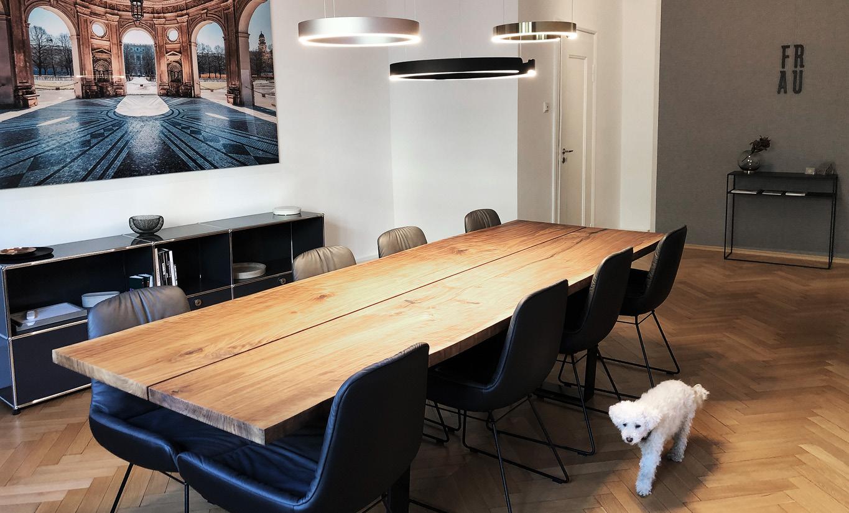 Großer Besprechungstisch aus Holz im Konferenzraum. Occhio Lampen an der Decke und ein großes Bild von München an der Wand. Im Vordergrund läuft ein Pudel.