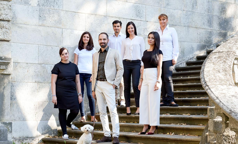 Alle Mitarbeiter der Kanzlei auf einem Gruppenbild. Die Gruppe steht auf einer Treppe am Friedensengel in München.